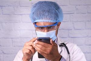 medico in maschera protettiva utilizza lo smartphone in ospedale foto