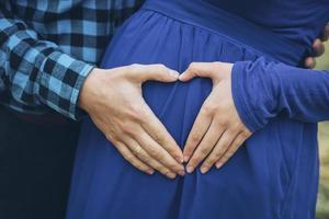 coppia incinta con le mani a forma di cuore