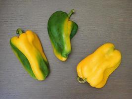 peperoni gialli e verdi su uno sfondo di tavolo in legno foto