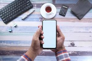mano che tiene smart phone su sfondo bianco foto