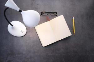 vista dall'alto di una lampada, un diario e una matita foto