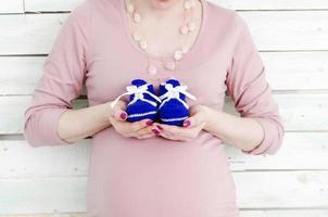 donna incinta che tiene scarpe per bambini blu foto