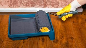 mano nel guanto giallo immerge il rullo in un vassoio con vernice grigia per dipingere i muri foto
