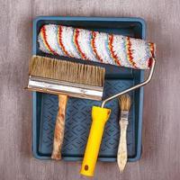 spazzole per dipingere pareti e soffitti rullo in vassoio su fondo grigio foto