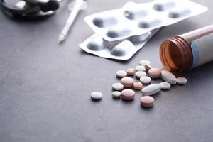 pillole e blister su sfondo nero foto