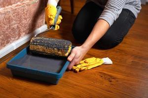 ragazza mette un rullo in un vassoio con vernice grigia in guanti gialli foto