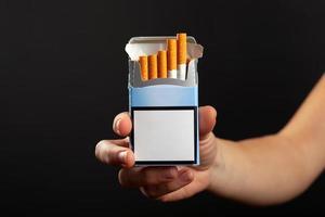 pacchetto di sigarette blu in mano su uno sfondo scuro, mockup foto