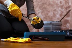 persona in guanti da lavoro gialli tiene il rullo sopra il vassoio con vernice grigia foto