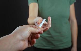 ragazzo dà a una ragazza una sigaretta su uno sfondo scuro foto