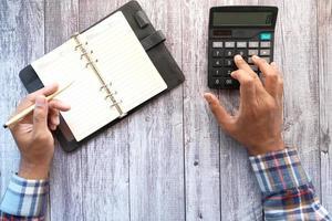 stretta di mano dell'uomo utilizzando la calcolatrice foto