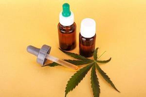 olio di canapa per uso medico, bottiglie con estratto di cannabis medica su sfondo giallo foto