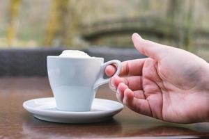 mano femminile che tiene il caffè foto