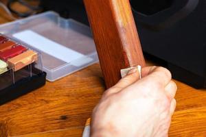 il maestro chiude il graffio di parquet laminato e mobili in legno foto
