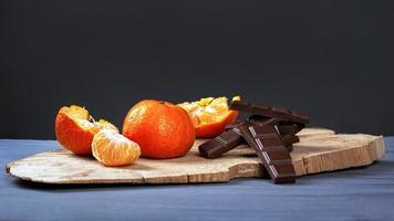 mandarini con cioccolato nero su supporto in legno su uno sfondo grigio scuro foto