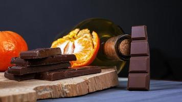 pezzi di cioccolato, mandarini e una bottiglia di vino su un piatto di legno foto