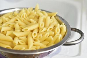 pasta italiana appena lavata in uno scolapasta in cucina foto