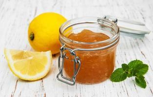 marmellata di limoni e limoni freschi su uno sfondo di legno foto