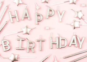 candele di buon compleanno su sfondo rosa