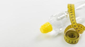 nastro di misurazione giallo e bottiglia d'acqua su sfondo bianco foto