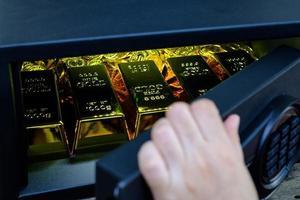 Cassaforte in acciaio con apertura a mano piena di monete lingotti d'oro foto