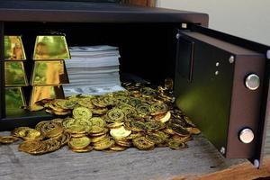 monete d'oro che fuoriescono dalla cassaforte foto