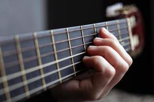 mani femminili sul collo di una chitarra acustica, suonare la chitarra foto