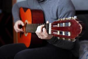 ragazza che suona una chitarra acustica a sei corde con corde di nylon foto