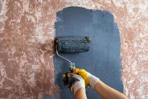 dipingere il muro con un rullo di vernice grigia foto