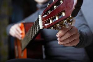 ragazza sintonizza un primo piano di chitarra acustica foto