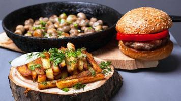 patatine fritte, hamburger e funghi fritti su uno sfondo grigio, close-up foto
