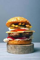 delizioso hamburger con una grande cotoletta di carne con verdure, formaggio e patatine fritte su uno sfondo grigio foto