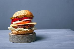 hamburger grande e succoso con panino fresco morbido, formaggio, verdure fresche e gustosa cotoletta di carne foto