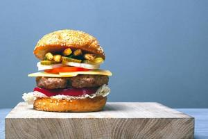 grande hamburger succoso con copia spazio su sfondo grigio foto