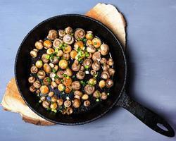 funghi champignon fritti in una padella di ghisa con cipolle verdi fresche su un supporto di legno foto