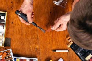 sigillando scheggiature e graffi sul laminato, il maestro corregge un difetto su un pavimento con cera e un saldatore foto