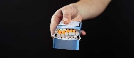 pacchetto di sigarette in mano su sfondo scuro con copia spazio foto