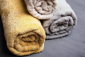 tre asciugamani piegati arrotolati color pastello su uno sfondo grigio foto