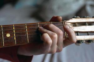 ragazzo suona una melodia su una chitarra acustica mentre si tiene la mano sulla tastiera foto