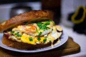 panino arrosto con salsiccia, uova, formaggio e cipolle verdi foto