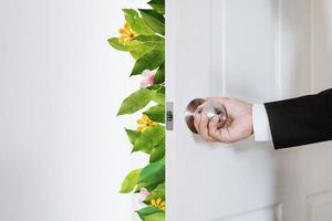 uomo d & # 39; affari che apre la porta, con foglie e fiori foto