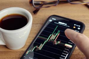dito che tocca un grafico del mercato azionario sullo schermo dello smartphone e una tazza di caffè sulla scrivania foto