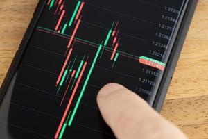 dito sul grafico del mercato azionario dello schermo di uno smartphone foto
