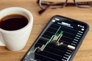 grafico del mercato azionario sullo schermo del telefono intelligente tazza di caffè e occhiali da vista foto