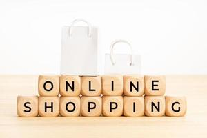testo dello shopping online su blocchi di legno sul tavolo e sacchetti di carta foto