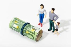 rappresentazione umana di una famiglia che guarda un rotolo di banconote foto