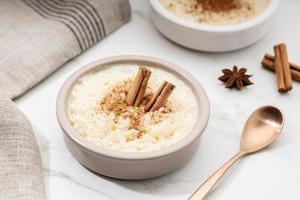 budino di riso cremoso con cannella in una ciotola sul tavolo di marmo bianco foto