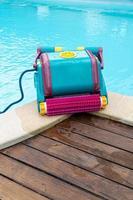 robot pulitore sul bordo di una piscina foto