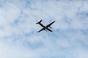 una bellissima vista di un aereo di linea wide-body passeggeri volante, un aeroplano, contro uno sfondo di nuvole bianche in un cielo estivo blu foto