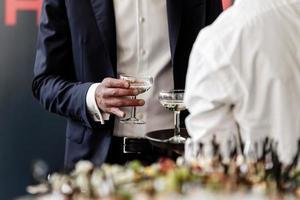 uomo d'affari bello e di successo in vestito elegante che tiene un bicchiere di martini a una festa, festa aziendale, conferenza, forum, banchetti, primo piano. messa a fuoco selettiva. foto