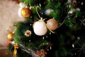 sfondo vacanze di Natale. Bagattelle dorate e bianche che pendono da un albero decorato con bokeh, spazio della copia foto